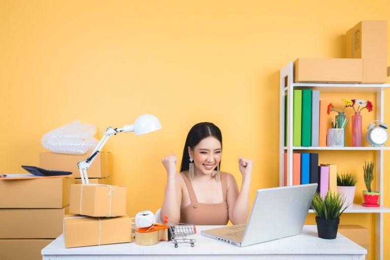 mulher-em-frente-ao-computador-comemorando-venda