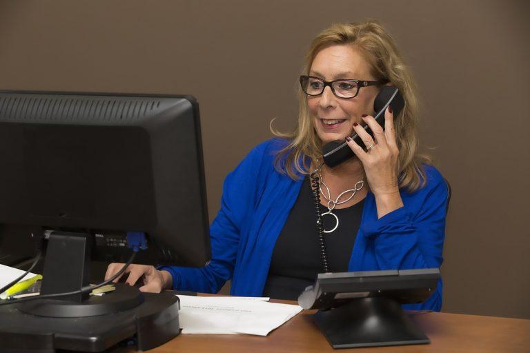 mulher-madura-em-frente-ao-computador-falando-ao-telefone